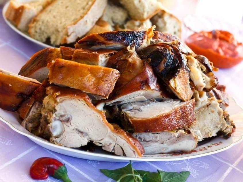 Cochon de lait à la broche, gousses d'ail, gros sel, persil en grande quantité et rondelles d'oranges.