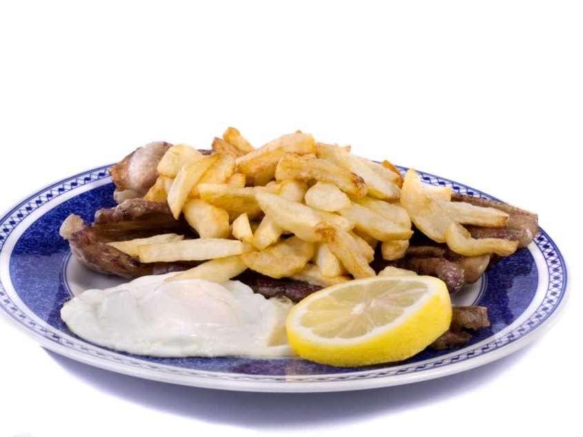 Viande de bœuf ou de porc frite, servie avec un œuf au plat, pommes de terre frites, riz et un mixte de salade verte, tomates et oigno